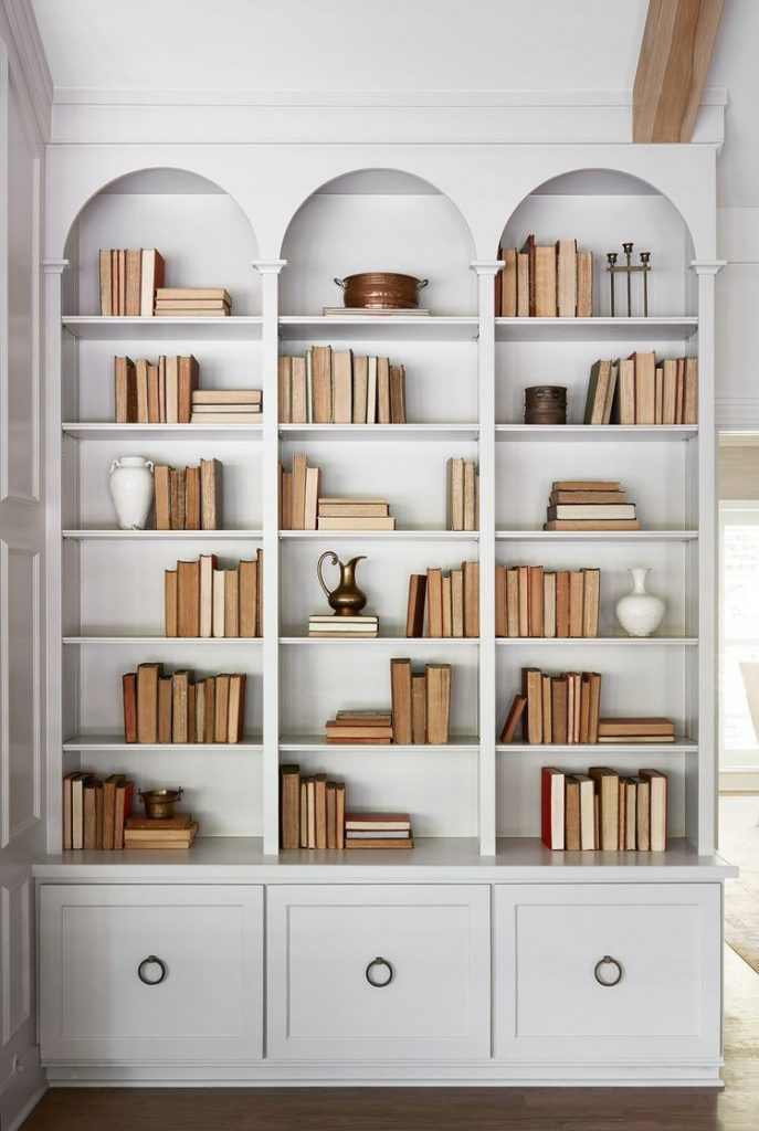Shelving unit split into three columns, with three arches at the top, open shelving and three closed cupboards along the bottom.