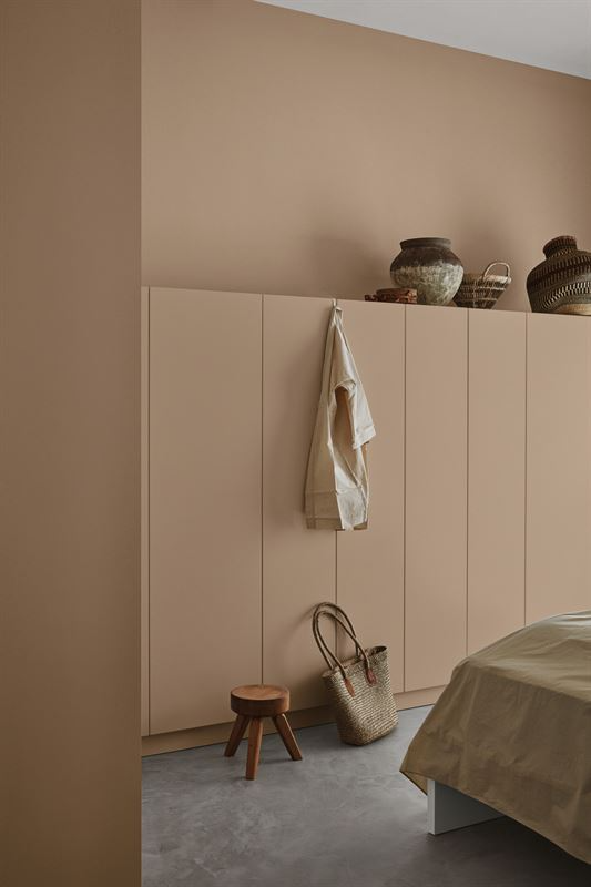 Hidden bedroom storage, cupboards which blend in with the painted wall behind.