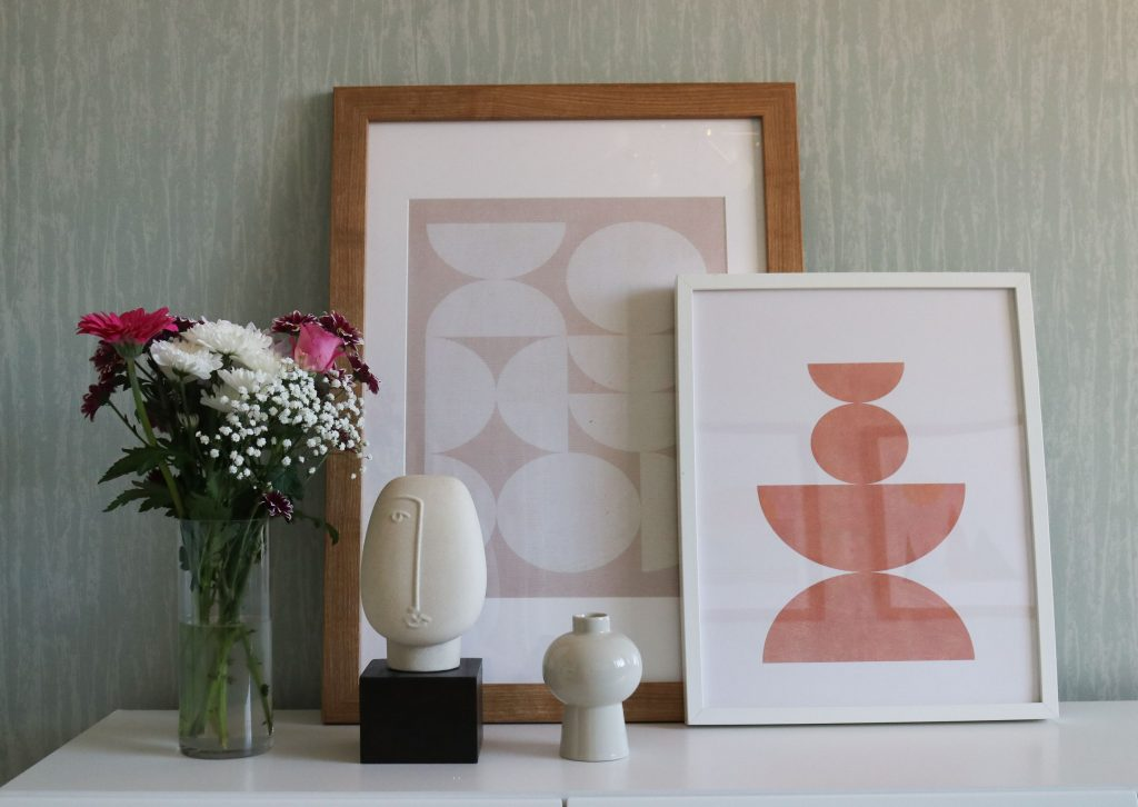 #Shelfie, shelf decorated with photo frames, vases and a face ornament.