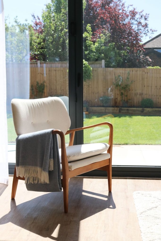 Armchair situated in front of bi-folding doors leading out onto patio